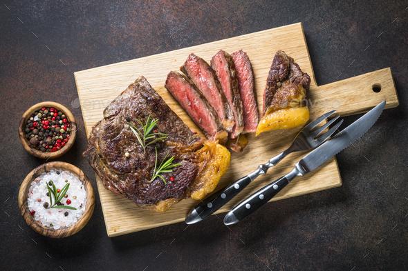 Grilled beef steak ribeye on wooden cutting board.